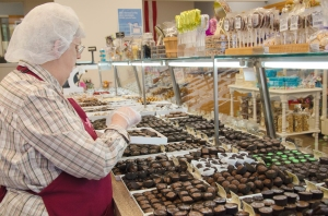 In the Wockenfuss Candies shop, a shop assistant is helping the consumer pack the candies.