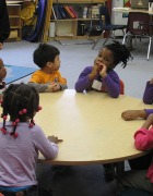 Children sit around a table waiting for a teacher.