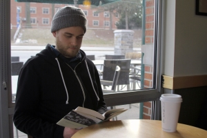 "Brendan Cathcart, 24, reads Joan Didion's ""The Year of Magical Thinking,"" at Towson's York Road Starbucks. Film industry workers can rarely find downtime for personal leisure given hectic production schedules (Photo by Mark Burchick)."