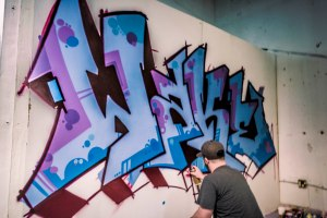 Mike Wake spray paints his tag.