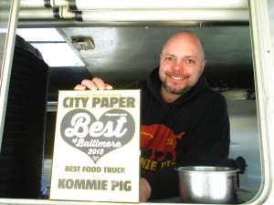"""Rob holds up the old City Paper that sits in the window of the Kommie Pig truck. He proudly smiles knowing that his truck won the award for """"Best Food Truck."""""""